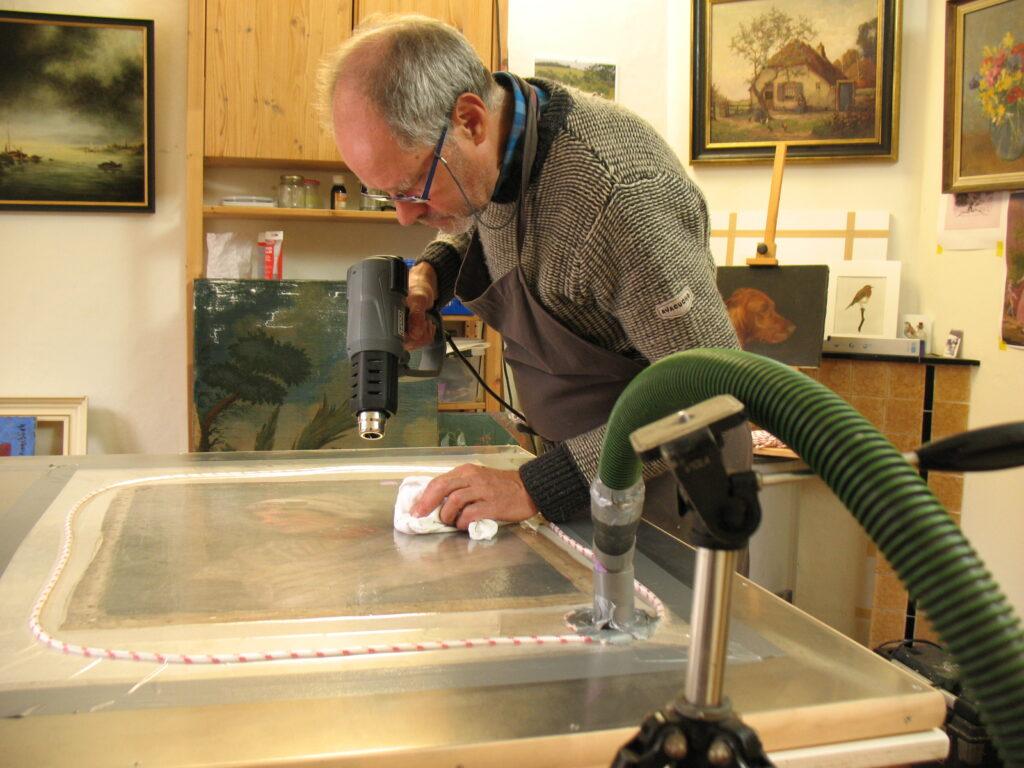 Bedoeken van een schilderij op een vacuümtafel. Door het geheel te verwarmen smelt de lijm en zorgt ervoor dat het oude doek op de nieuwe ondergrond hecht.
